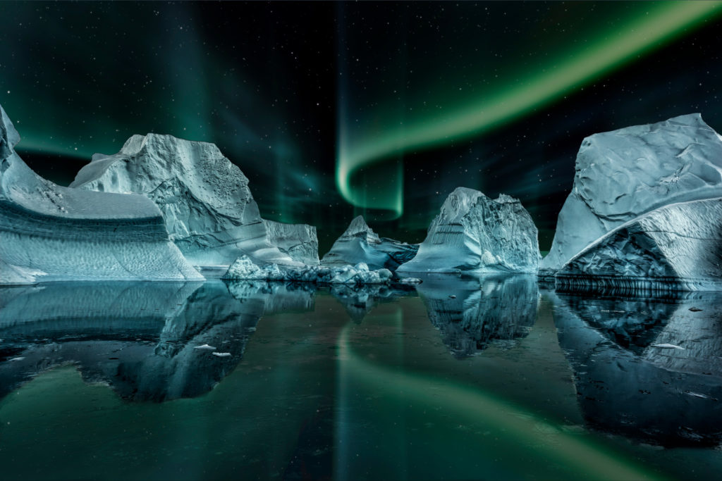 Iceberg,Floating,In,Greenland,Fjord,At,Night,With,Green,Northern